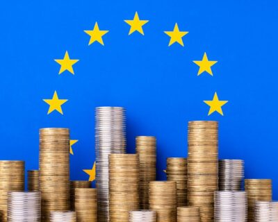 Piles of golden and silver coins on the background of european union flag. Economy in EU concept.